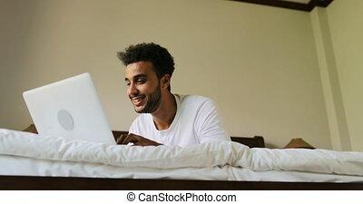 bavarder, ordinateur portable, chambre à coucher, jeune, lit, matin, hispanique, informatique, ligne, utilisation, homme souriant, type, mensonge, heureux