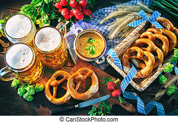 Bavarian beer with soft pretzels, obatzter and radish on rustic wooden table