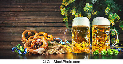 Bavarian beer with soft pretzels, wheat and hop on rustic wooden table