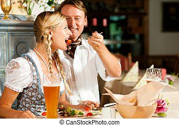 Bavarian Couple in restaurant eating