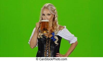 Bavarian girl drinking beer. Green screen