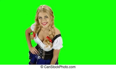 Bavarian girl in bavarian costume offers a beer to someone. Green screen