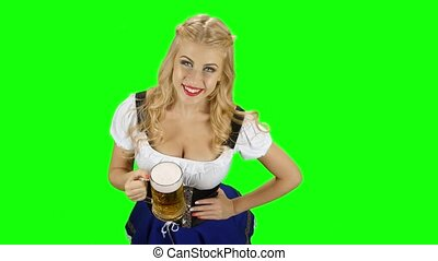 Bavarian girl in bavarian costume holding a glass of beer and laughs. Green screen