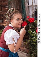 Bavarian girl in dirndl smelling a