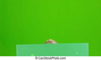Bavarian girl looks out from behind the green board. Green screen