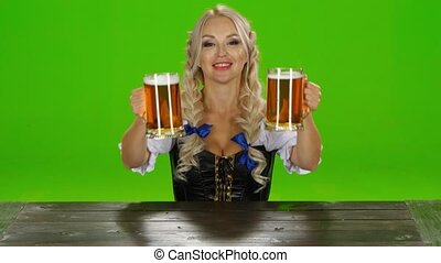 Bavarian girl puts on the table two glasses of beer. Green screen