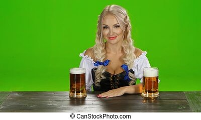 Bavarian girl sitting at a table with two glasses of beer....