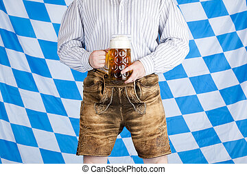 Bavarian man with Oktoberfest beer stein (Mass) and leather ...