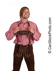 Bavarian man with oktoberfest leather trousers (lederhose) holds suspenders. Isolated on white background.