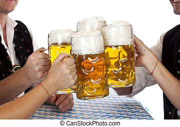 Bavarian men and women toast with Oktoberfest beer stein....