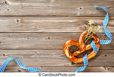 Bavarian pretzel with ribbon and edelweiss on wooden board....