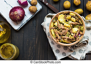 Bavarian salad with smoked meat on a dark background