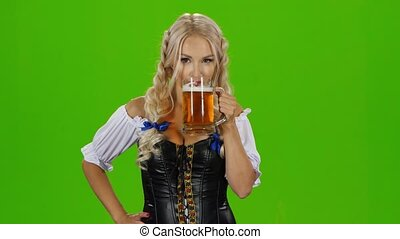 Bavarian woman drinking a beer glass showing thumbs up and winking. Green screen