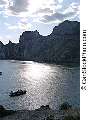 bay in the black sea on the background of steep cliffs covered with grass. Walking on a boat