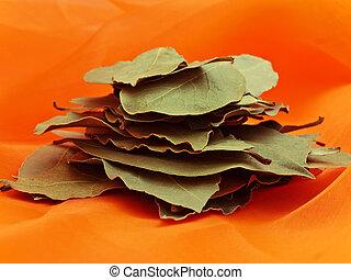 bay leaves - Photo of bay leaves stack at orange textile
