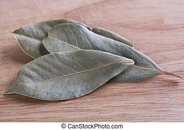 Bay Leaves - Dried bay leaves on wooden board.
