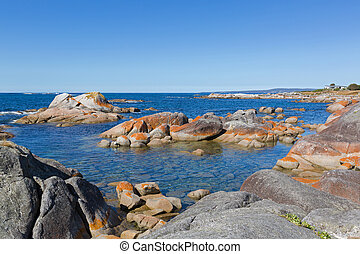 Bay of Fires. Turquoise waters with orange lichen growing on...