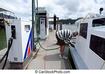 Man fuels his boat - BAY OF ISLANDS, NZ - DEC 12:Man fuels...