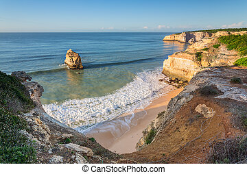 Bay on the ocean with beautiful blue waves. Portugal Algarve.