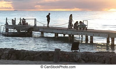 People on pier at sunset