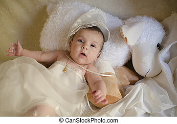 Bbay with christening cap lying, baptism clothes.
