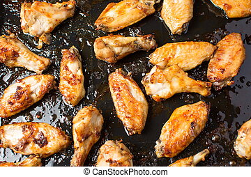 bbq chicken wings on a black plate