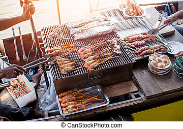 BBQ grill seafood on boat at Amphawa river market in ...