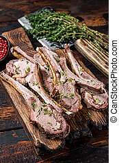 BBQ Grilled Lamb Ribs Chops steaks on butcher board with meat cleaver. Dark wooden background. Top view