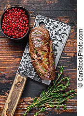BBQ Grilled veal sirloin meat steak on a meat cleaver with herbs. Dark wooden background. Top view