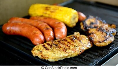BBQ grilling - Grilling of a chicken steak, sausages and...