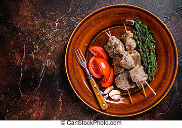 Bbq lamb meat on wooden skewers with vegetables on a rustic plate. Dark background. Top view. Copy space