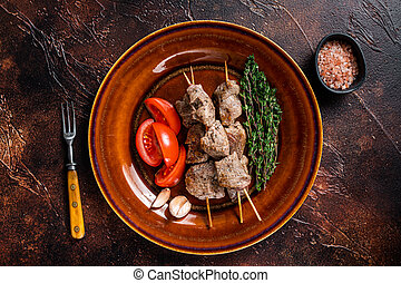 Bbq lamb meat on wooden skewers with vegetables on a rustic plate. Dark background. Top view
