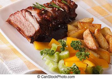 BBQ pork ribs with salad and fried potatoes close-up. horizontal