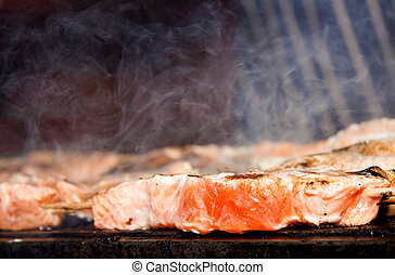 BBQ salmon. - Fresh salmon being cooked on an outdoor...