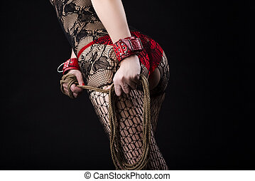 BDSM Accessories and Concepts. Back of Caucasian Female in Sexy Lingerie Posing with Rope for BDSM Role Game.In red Handcuffs and Net Pantyhose.
