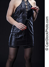 BDSM Concepts and Ideas. Mature caucasian Female Shows Off Clothing and Accessories for Sado-Masochism. Posing with Leather paddle Against Black.