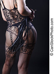 BDSM Concepts and Sex Toys Ideas. Back View of Caucasian Woman in Sexy Lingerie Posing with Leather Lash for BDSM Role Game.