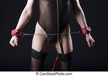 BDSM Concepts. Front View of Mature Caucasian Female Posing with  Accessories for Sado-Masochism Play. Tied with Chain and Wristbands. Against Black.