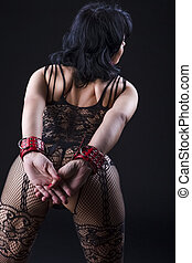 BDSM Ideas. Back View of Alluring Caucasian Female in Sexy Mesh Body Suit Prepared for Sado-Masochism Play. Bent Forward Over Black Background.