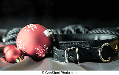 bdsm still life leather collar and christmas balls on silver fabric close up
