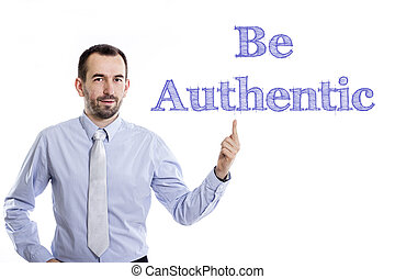 Be Authentic - Young businessman with small beard pointing up in blue shirt