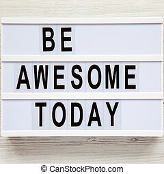 'Be awesome today' word on modern board over white wooden surface, from above. Flat lay, overhead, top view.