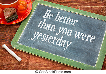 Be better than you were yesterday - motivational text on a slate blackboard with chalk and cup of tea
