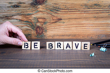 Be Brave. Motivation, inspiration, purpose and ability to act. Wooden letters on the office desk, information and communication background