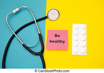 Be healthy - advice on pink sticky note near stethoscope and tablets. Concept of health life style