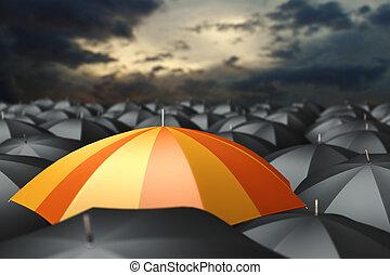 Orange umbrella in mass of black umbrellas