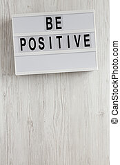 'Be positive' words on a lightbox on a white wooden background, top view. Overhead, from above, flat lay. Copy space.