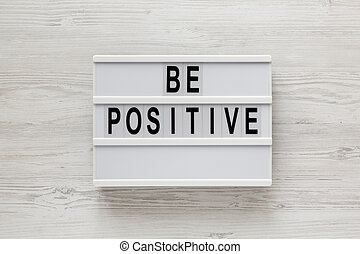 'Be positive' words on a lightbox on a white wooden background, top view. Overhead, from above, flat lay.