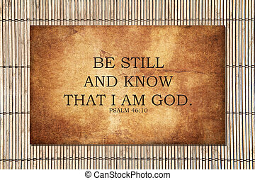 """The bible Psalm scripture from 46:10 says """"Be still and know that I am God."""" Motivational and encouraging. Strong text over a stone background, with bamboo outside."""