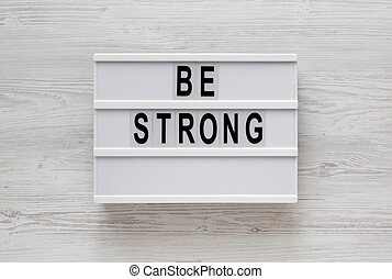 'Be strong' words on a lightbox on a white wooden background, top view. Overhead, from above, flat lay.